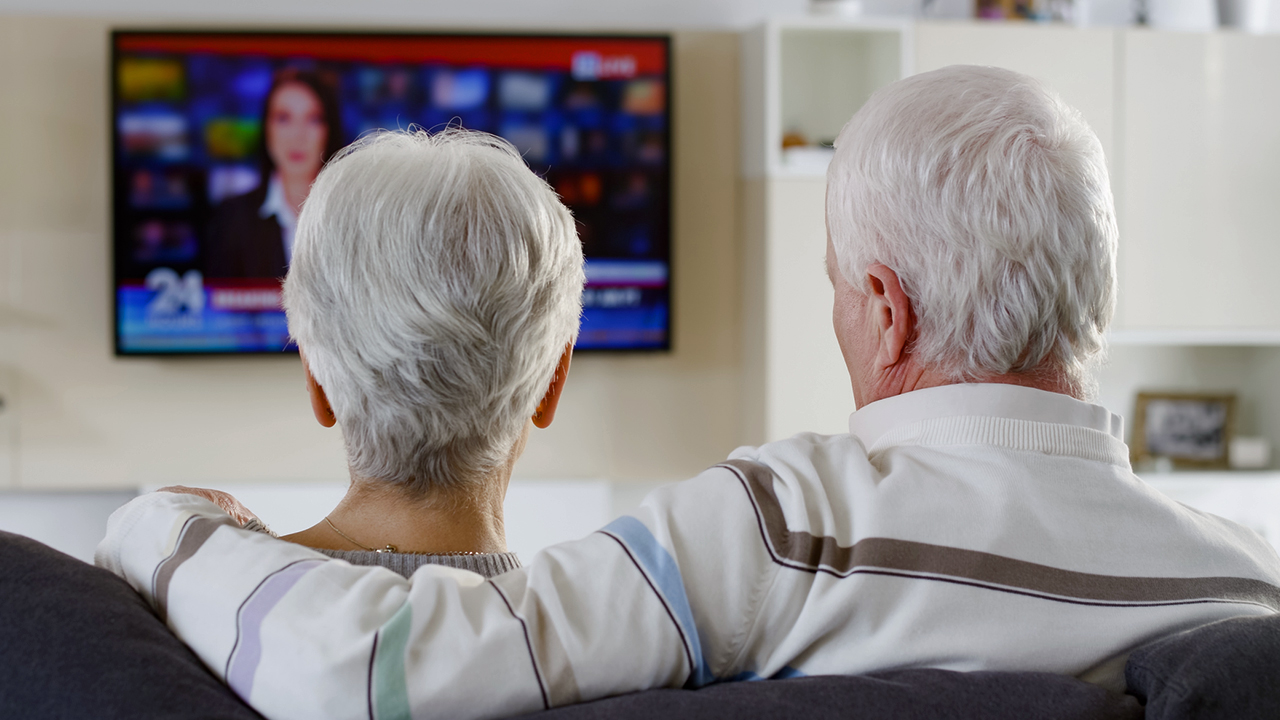 A photo of a couple watching local news on TV.