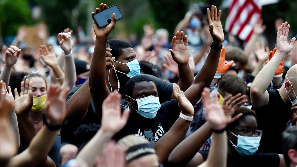Protesters kneel and hold up their hands in Lafayette Square, near the White House, on June 4 to protest the death of George Floyd. (Olivier Douliery/AFP via Getty Images)