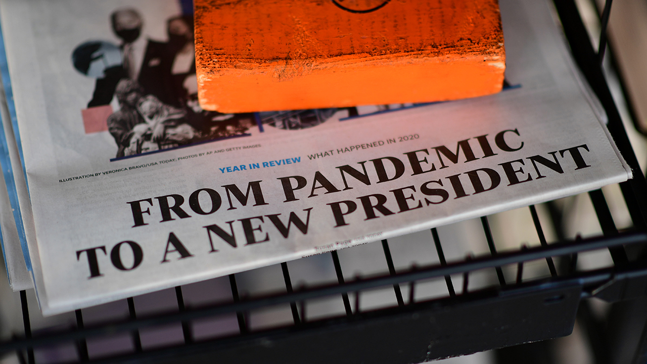 """The front page headline of a newspaper states """"FROM PANDEMIC TO A NEW PRESIDENT"""" on December 31, 2020 in Rehoboth Beach, Delaware. (Mark Makela/Getty Images)"""